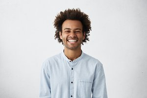 Handsome unshaven young dark-skinned male laughing out loud at funny meme he found on internet, smiling broadly, showing his white straight teeth. Positive human facial expressions and emotions