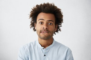 Headshot of attractive mixed race male student with stubble and tousled hair biting his lower lip in impatience having worried and scared look, can't wait for results of final examination at college