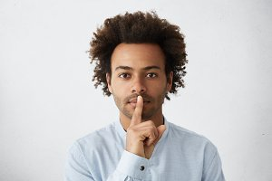 Afro American businessman in formal wear keeping index finger on his lips, asking to hold tongue and keep private confidential information, looking at camera with serious expression. To secret