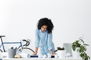 People, job and career. Indoor shot of talented woman engineer leaning hands on her desk checking blueprints with focused look, standing against white wall background with copy space for your text