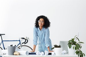 Cheerful young dark-skinned female interior designer wearing stylish glasses and blue shirt standing at her workplace, placing hands on desk after finished working on new project, smiling happily