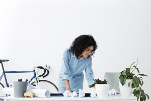Smiling African American young woman engineer using laptop at office, standing and working with drawings on table, isolated against background of white wall and bicycle. Education and business concept