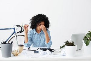 Tired black woman with glasses in hand rubbing eyes, full of sad restless thoughts, feeling stressed calculating her debt for rent, making notes, isolated on background of home interior and bicycle