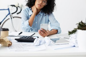 Cropped shot of African American young female freelancer sitting at home at working table with contemporary gadgets, chatting with boss about her payment, comparing their results using calculator