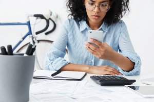 Serious young female employee in stylish glasses sitting at her desk and using mobile phone, looking at screen with concentrated expression during working day in office, bicycle in background