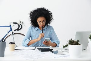 Frustrated young female entrepreneur in formal shirt and eyewear having a problem while working on financial report in office, reading information on mobile phone screen with perplexed expression