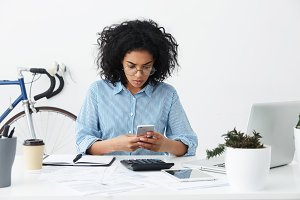 People and modern technologies concept. Concentrated young mixed race female secretary reading urgent message on cell phone while sitting at her workplace with electronic gadgets and papers