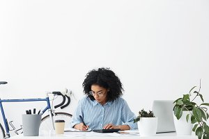 Attractive young African American female accountant wearing blue shirt and eyeglasses working on financial report at her white office, making calculations and hand writing, looking concentrated