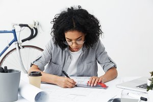 Hardworking cand oncentrated young female architect drawing line on blueprint using pen and ruler, having another coffee, trying to finish project by the end on working day, sitting at her desk