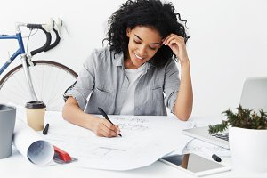 Vocation and creativity. Cheerful young Afro American woman designer with charming smile making notes on sketches on table in front of her, feeling excited and happy about doing what she likes