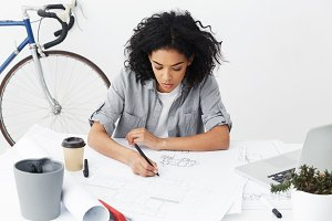 Top view of beautiful young African American woman architect making drawing of new house development project. Stylish hardworking dark-skinned female engineer siting at desk with blueprints