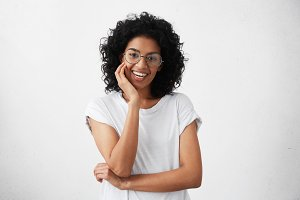 Positive friendly looking young mixed race woman with curly brunette hair smiling cheerfully as she listens to good news while talking to her best friend, posing at white wall, keeping hand on cheek