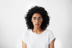 Studio shot of frightened bug-eyed young female feeling scared and shocked, watching horror movie. Attractive dark-skinned woman dressed casually having terrified look while receiving shocking news