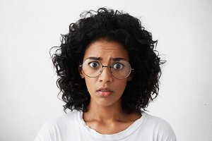 Human emotions, feelings, reaction and attitude. Startled mixed race girl wearing big round glasses looking at camera with shocked expression, afraid of sudden noise while staying home alone