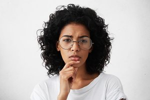 Let me see. Beautiful young woman in white t-shirt and big round spectacles squeezing her eyes in pensive expression, touching her chin while making choice or taking serious important decision