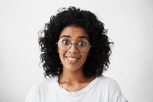 Headshot of funny young mixed race female with curly hair wearing stylish eyeglasses looking at camera with beseeching or shocked expression, raising her eyebrows. Human emotions and feelings