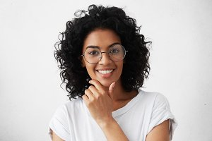 People and lifestyle. Youth and happiness. Close up portrait of confident dark-skinned girl with curly hairstyle posing against whit