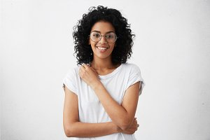 Attractive mixed race female actress wearing round eyeglasses and t-shirt looking and smiling at camera in closed posture, keepings arm on her breast, standing against white wall during audition