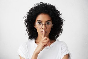 Worried serious dark-skinned girl wearing casual t-shirt and stylish round spectacles holding index finger at her lips, asking to keep silent and not to make noize. Human facial expressions