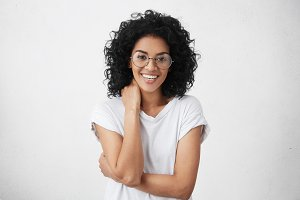People, lifestyle, happiness and youth concept. Attractive young mixed race woman with charming smile wearing trendy eyeglasses feeling happy and carefree while relaxing indoors after working day