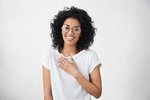 Happy beautiful warm-hearted young dark-skinned female wearing big round spectacles and white t-shirt smiling and holding hand on her breast while watching touching romantic scene in TV series