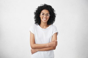 Human facial expressions, emotions, feelings, reaction and attitude. Attractive happy mixed race girl wearing her shaggy hair loose, holding arms folded in front of her, rejoicing at good news