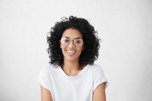 Close up isolated studio shot of good looking cheerful positive young mixed race female with brunette curly hair, smiling broadly, showing her white teeth at camera while having fun indoors