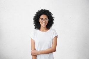 Relaxed carefree smiling young woman wearing white t-shirt and glasses having positive cheerful expression on her face, rejoicing at her leisure time, spending day at home. Horizontal studio shot