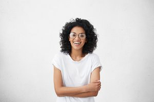 Indoor portrait of beautiful young dark-skinned woman wearing big round eyeglasses and casual white t-shirt smiling joyfully, keeping arms crossed, laughing out loud while watching comedy on TV