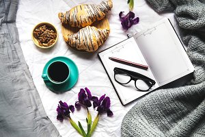 Breakfast in the bed. Morning, croissant, coffee, flowers and a notebook with a pen. Planning