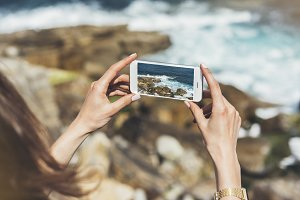 Girl makes a photo on the smartphone