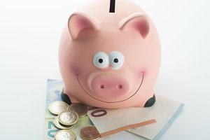 Piggy bank on banknotes and coins on white background. Isolated.