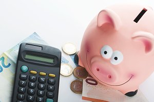 Piggy bank on banknotes and coins next to a calculator on white background.
