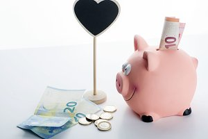 Piggy bank, coins, bills and a poster with heart shape on white background. Isolated.