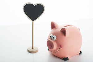 Piggy bank and a poster with heart shape on white background. Isolated.