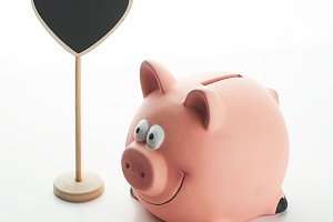 Piggy bank, coins and a sign with heart shape on white background. Isolated.