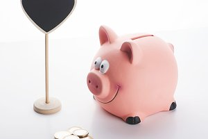 Coins next to a piggy bank and a poster with heart shape on white background. Isolated.