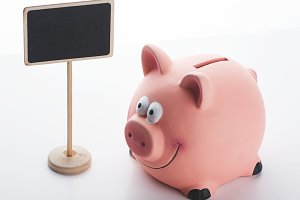 Piggy bank on white background next to a poster. Copy space.