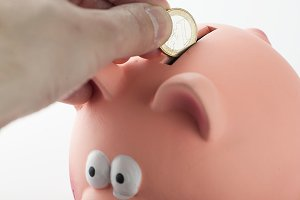 Male hand inserting a coin into a piggy bank.