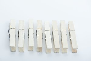 Wooden clothespins in line on white background. Isolated.