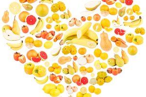 Different yellow and orange fruits and vegetables in the shape of the heart