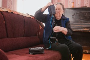 An elderly woman prepares the device for measuring blood pressure