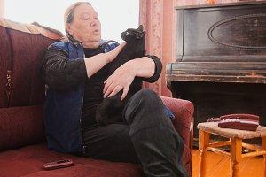 Elderly woman petting black cat