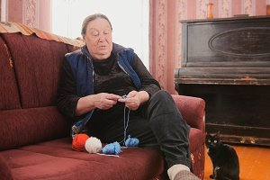 Elderly woman picking up loops on the needles - knits a wool