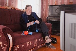 Elderly woman in glasses knitting in front of the TV