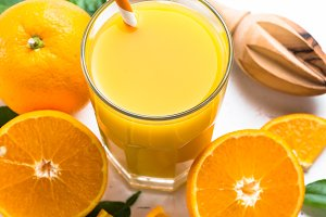 Orange juice in glass on white.