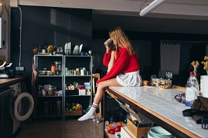 Blond girl in red sweater in kitchen