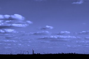 Industrial landscape - silhouette in front of clouds, cooled toned