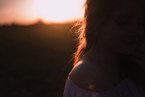 Beautiful young woman with a bouquet of lavender and dreaming in the sunset rays