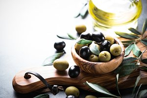 Black and green olives in wooden bowl